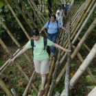 Journalist walking across a bamboo bridge
