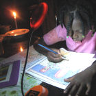 A girl uses a Barefoot Power solar-powered lamp