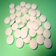 Round, biconvex white tablets