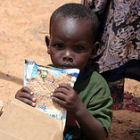 Child in Somalia receiving food distributed by FMSC and GAiN