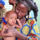 A woman and child receive humanitarian assistance in the Sahel