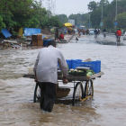 Man pushing barrow in Indian monsoon