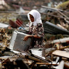 Woman searches through wreckage in the aftermath of Indian Ocean tsunami