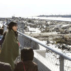 A woman in Japan surveys devastation wrought by the 2011 tsunami