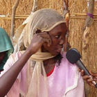 A journalist interviewing a woman in Africa