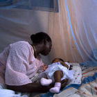 Mother with child under bednet