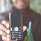 A Kenyan woman holding a mobile phone