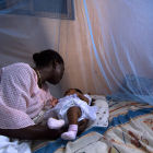 Mother and child under malaria bednet, Ghana