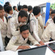Schoolchildren around laptops, Indonesia