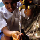 Boy getting water from community pipe, Sri Lanka