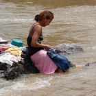 Woman washing clothes in river