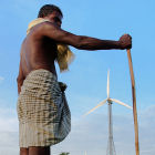 A farmer stands in front of a wind farm/India