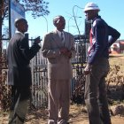 Three african men standing outside in suits