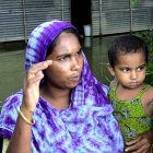 A Bangladeshi mother and child outside a flooded home