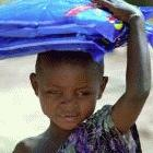 Boy carrying bednets: the nets should be made free of charge, say Sachs and colleagues