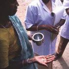 A woman takes medication as part of an attempt to control the spread of filariasis