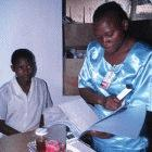 A researcher in Kenya checks a patient's records before giving her a tablet
