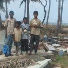 Sri Lankan tsunami eyewitnesses on remains of a house destroyed by the waves