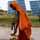 Woman collects water from a solar powered water pump in India