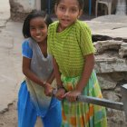 Indian children pumping water