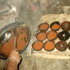 Jaggery production - pouring the boiled treacle into coconut shells to produce the hardened solid form of it
