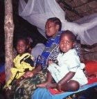 A mother and her daughters under a bednet in Tanzania