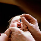 Baby, visiting doctor, receiving oral polio vaccine