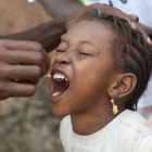 Girl receiving oral polio vaccine