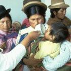 A doctor administers oral rehydration solution to a Peruvian child