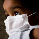 Small child wearing a swine flu mask