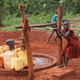 Children collect water from a small local well in their Ugandan village